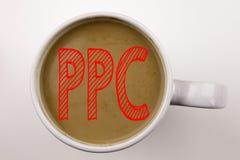 Ordet som skriver PPC - betala per klicktext i kaffe i kopp Affärsidé för internet SEO Money på vit bakgrund med kopieringsbrunns royaltyfria foton