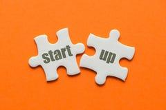 Ordet startar upp på matcha pussel två på orange bakgrund Arkivfoton