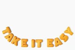 Ordet TAR LÄTT för IT som göras med alfabetet formade kex som isoleras på vit bakgrund med fritt utrymme för text royaltyfri foto