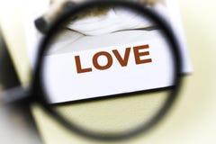 Ordförälskelse i förstoringsglas Förälskelsesökandebegrepp royaltyfri foto