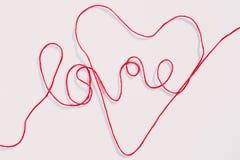 Ordförälskelse och hjärtaform som är skriftlig med rött garn, dragar på vit arkivbild