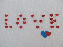 Ordförälskelsen från röda hjärtor i snön Royaltyfri Foto