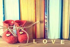 Ordförälskelsen många hjärtor på en bakgrund av böcker på en trätabell röda skor Royaltyfri Foto