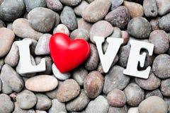 Ordförälskelsen med röd hjärta på kiselstenstenar Royaltyfri Bild