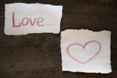 Ordförälskelsen och hjärtan dras i röd blyertspenna på ett stycke av papper allt lokaliseras på ett träbräde fotografering för bildbyråer