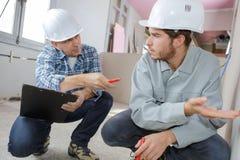 Ordförandebyggmästare och byggnadsarbetare med ritningen i inomhus lägenhet royaltyfri foto