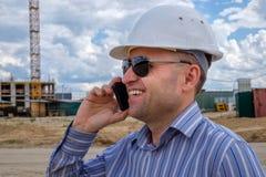 Ordföranden i den vita hjälmen på konstruktionsplatsen talar på en mobiltelefon fotografering för bildbyråer