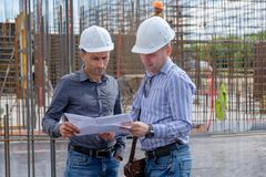 Ordföranden och leverantören ser projektet på konstruktionsplatsen royaltyfri fotografi
