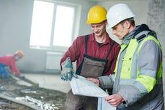 Ordförandebyggmästare och byggnadsarbetare med ritningen i inomhus lägenhet Arkivbilder