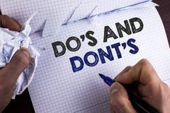 Ordhandstiltext Do och Don'Ts Affärsidé för vad kan göras och vad inte kan veta högert fel skriftligt vid mannolla Royaltyfri Foto