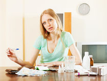 Ordinary  blonde woman with medications and money Royalty Free Stock Photo