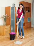 Ordinary brunette woman washing  floor with mop Royalty Free Stock Image