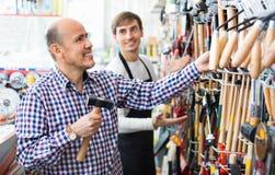 Ordinary cheerful customer and friendly seller choosing hammer Royalty Free Stock Photo