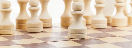 Ordinary chess. Pieces carved from wood. photo close-up, focus on the front pawn. background is out of focus Stock Photos
