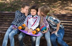Ordinary children whispering in park on bench in autumn royalty free stock photos
