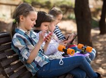 Ordinary children playing with the phone on bench outdoors royalty free stock photos