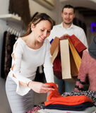 Ordinary couple choosing clothes at market Royalty Free Stock Photos