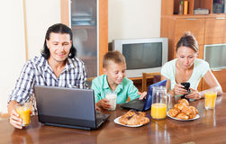 Ordinary couple with teenager son. Happy ordinary couple with teenager son using devices during breakfast at home Stock Photo
