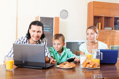Ordinary couple with teenager son using devices during breakfast Royalty Free Stock Images