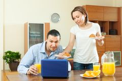 Ordinary couple using laptop during breakfast Royalty Free Stock Image