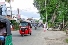 ordinary day on street in small Asian village, people move on their business on a motorcycle, tuk tuk. stock images
