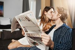 Ordinary day of two adult people in love, leaving together and spending their leisure at home. Man wants read newspaper. But girlfriend distracts him with kiss Royalty Free Stock Photo