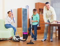 Ordinary family doing house cleaning. Ordinary family of three with teenager doing house cleaning with  cleaning equipment Stock Image