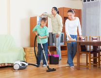 Ordinary family doing housework together. Ordinary family of three doing housework together in home Stock Images