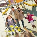 Ordinary family spending time at children swings. Ordinary family of four spending time together at children swings Stock Images
