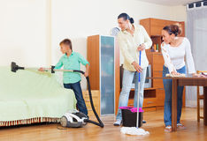 Ordinary family of three  doing house cleaning Royalty Free Stock Photo