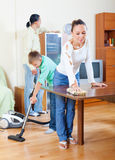 Ordinary family of three doing house cleaning Stock Photo