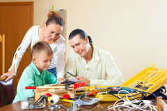 Ordinary family of three doing something with the working tools Stock Image