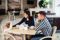 Ordinary family of three with little daughter and father mother giving solace at cafe during lunch Royalty Free Stock Photo