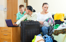 Ordinary family of three with luggage choosing the tickets on th Royalty Free Stock Photos