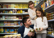 Ordinary family of three purchasing canned food. At supermarket. Focus on man Royalty Free Stock Images