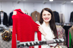 Ordinary female buyer choosing sweater. At clothing store Royalty Free Stock Photo