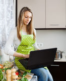 Ordinary girl in apron cooking with notebook Royalty Free Stock Photos