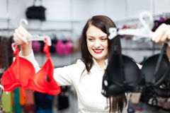 Ordinary girl choosing bra at fashion shop Royalty Free Stock Photography
