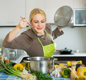 Ordinary girl cooking with vegetables. Portrait of ordinary girl cooking with vegetables Royalty Free Stock Photography