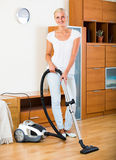 Ordinary girl hoovering at home Stock Photography