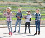 Ordinary girl jumping while jump rope game. With friends outdoor Royalty Free Stock Photography