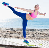 Ordinary girl stretching muscles on the sand Stock Image