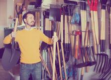 Ordinary guy deciding on best shovel. In garden equipment shop Royalty Free Stock Image