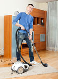 Ordinary guy with vacuum cleaner on parquet floor Stock Images