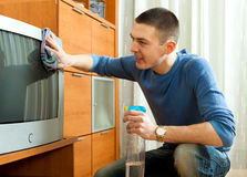 Ordinary guy wiping the dust on TV Stock Image