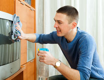 Ordinary guy woman dusting TV Royalty Free Stock Image