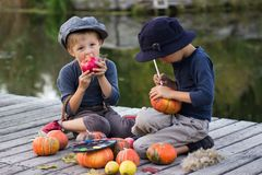 Ordinary kids paint small Halloween pumpkins. On the river bank Stock Photography