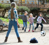 Ordinary kids playing street football outdoors Royalty Free Stock Photography
