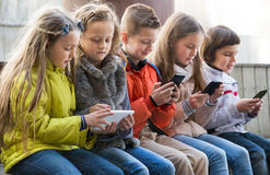 Ordinary kids sitting with mobile devices. In street Stock Images