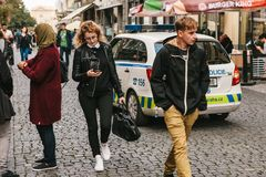 Prague, September 25, 2017: Ordinary life in the city. People walk along the street, next to the police car of the local. Ordinary life in the city. People walk Stock Photo